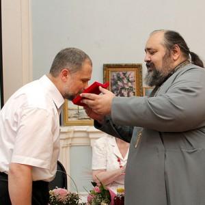 Отец Георгий Горлов вручает юбиляру складень икон Божией Матери и святителя Луки